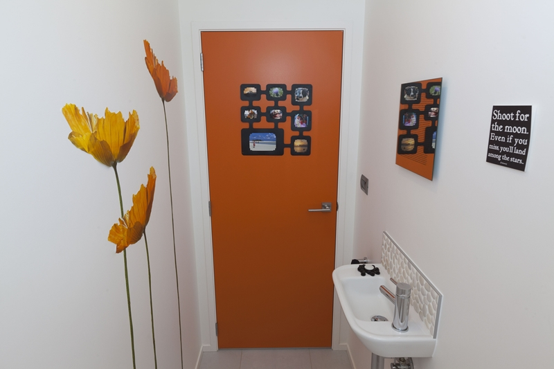 A splash of orange in this bathroom turns bland into beautiful.