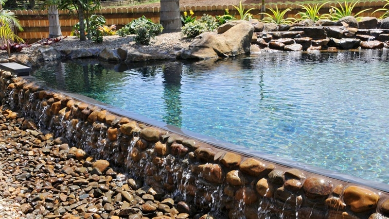 Rock features bring an organic, timeless feel to swimming pools.