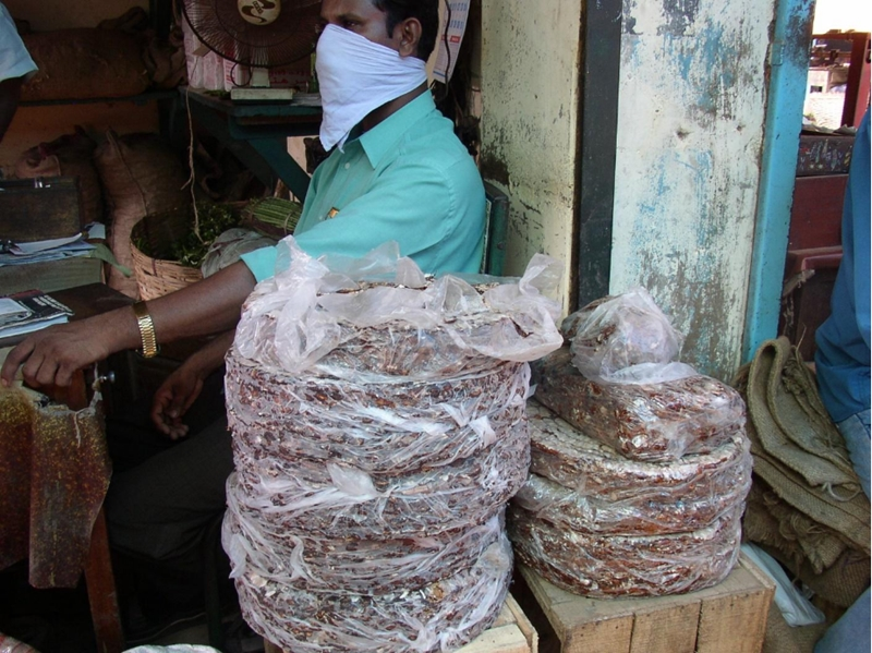 Huge wheels of compressed oxidized tamarind in a Cochin market in Kerala, South India.