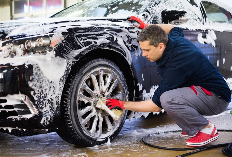 Man washing wheel of car with sponge.