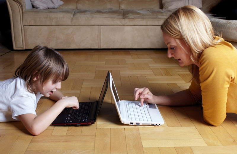 A parent and child each use laptops.