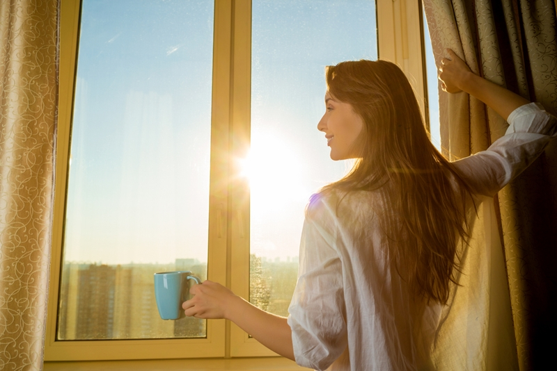 Woman drinking coffee, looking out the window.