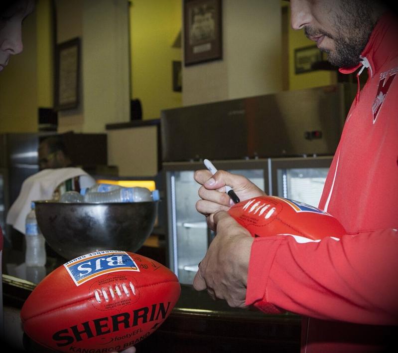 Man signs AFL balls