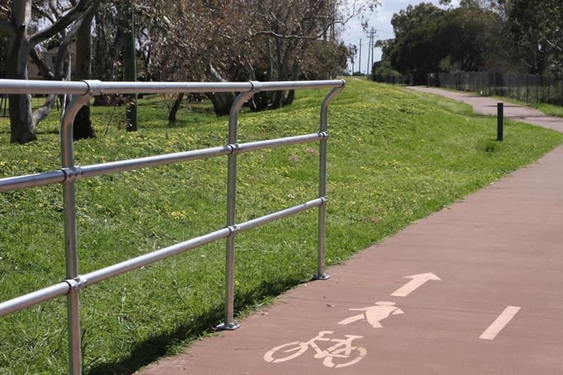 A handrail on a bike and pedestrian path.